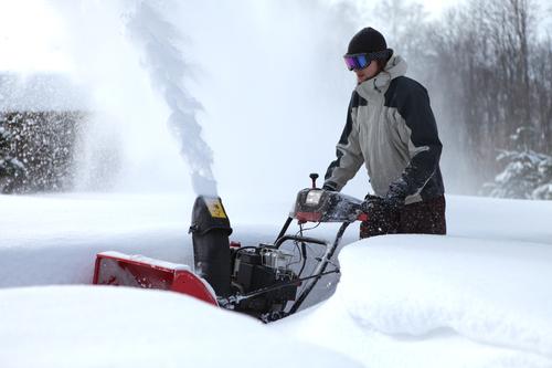 Mann beim Schneeräumen